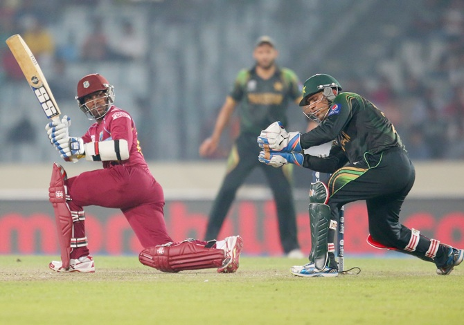 Denesh Ramdin bats as Kamran Akmal of Pakistan looks on