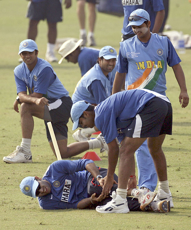 Indian players watch teammate Yuvraj Singh lying on the ground after he was injured during a training session during the ICC Champions trophy cricket tournament in Mohali on October 28, 2006