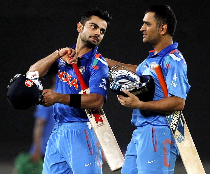 Virat Kohli (left) and Mahendra Singh Dhoni walk back at the end of India's innings in Sunday's final.
