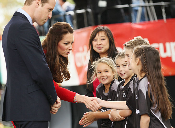 Kate Middleton shakes hands with young Henry Allott as Prince William watches Latimer Square on Monday