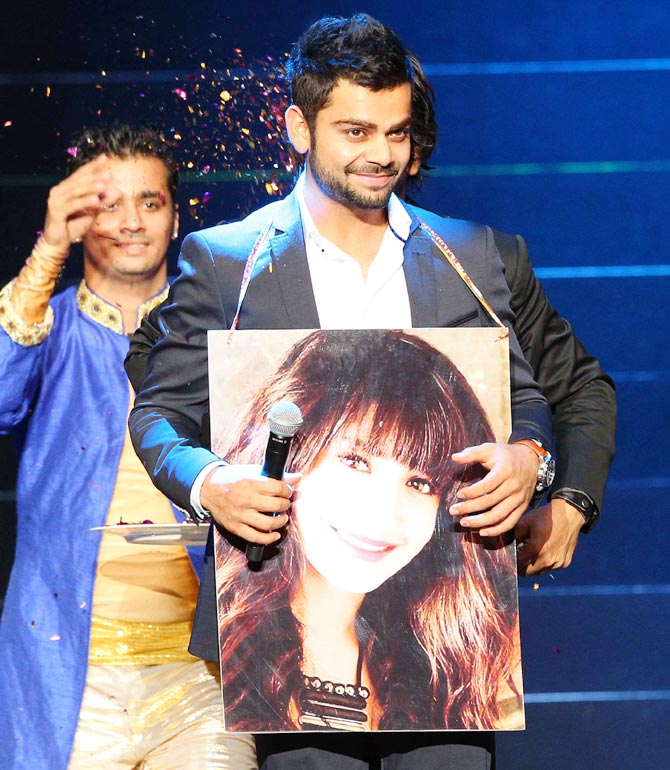 Virat Kohli with a poster of Anushka Sharma