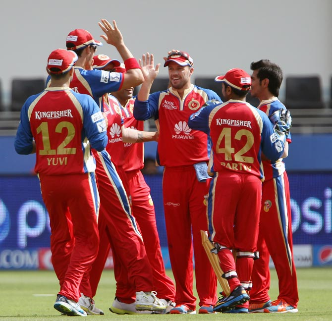 Royal Challengers Bangalore players celebrate the wicket of Rohit Sharma