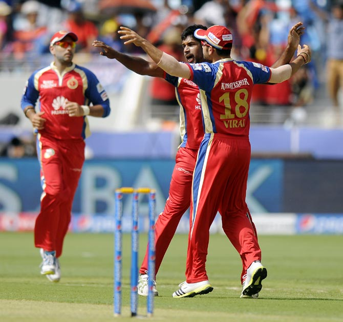 Varun Aaron celebrates with captain Virat Kohli after taking the wicket of Aditya Tare