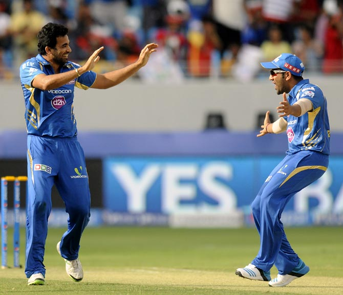 Zaheer Khan celebrates the wicket of Virat Kohli with captain Rohit Sharma (right)