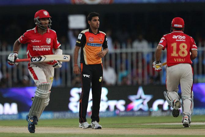 Cheteshwar Pujara and Virender Sehwag steal a single as Bhuvneshwar Kumar looks on