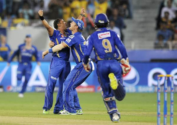 Pravin Tambe (left) is hugged by Shane Watson after taking the wicket of Mahendra Singh Dhoni