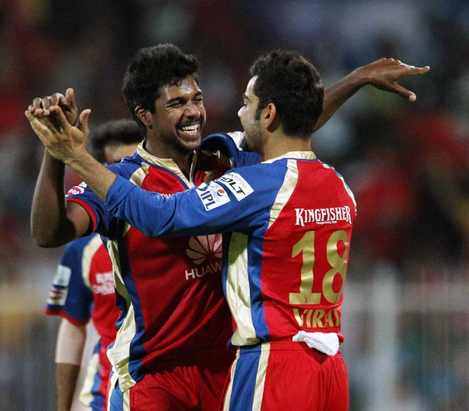 Varun Aaron celebrates with captain Virat Kohli after taking the wicket of Robin Uthappa