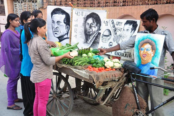 A vegetable seller with Sachin Tendulkar's portraits to celebrate his birthday in Moradabad