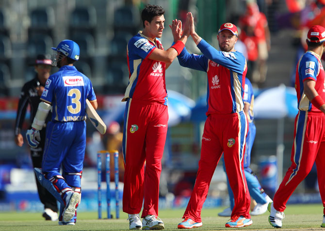 Mitchell Starc celebrates with Bangalore teammate AB de Villiers