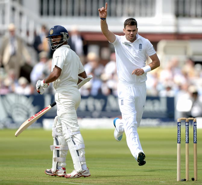 England fast bowler James Anderson (right) celebrates as Shikhar Dhawan walks after his dismissal during day one of the second Test match at Lord's
