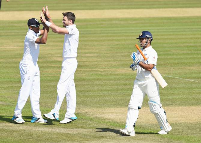 James Anderson (right) is congratulated by Chris Jordan after taking the wicket of Mahendra Singh Dhoni