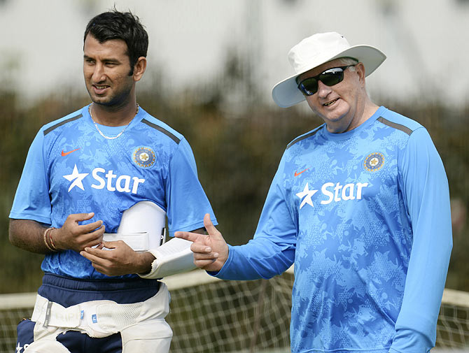India's Cheteshwar Pujara talks to coach Duncan Fletcher (right) during a training session on Tuesday