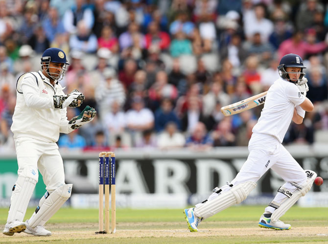 Joe Root cuts a ball to pick up some runs, watched by India wicketkeeper Mahendra Singh Dhoni