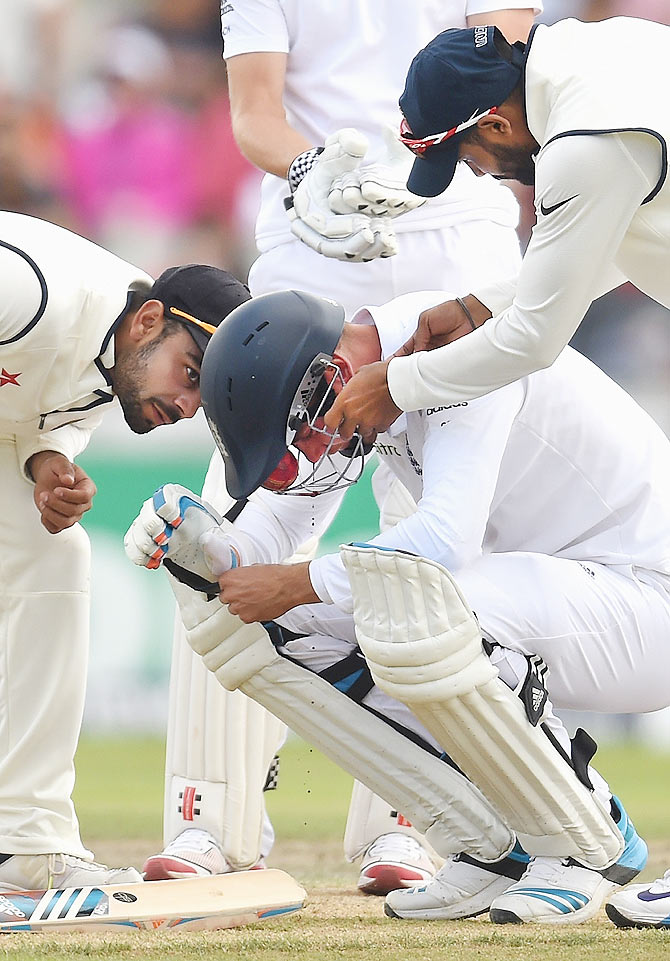 Indian fielders attend to England batsman Stuart Broad after he is hit, by a Varun Aaron delivery, through the grill of his helmet in the fourth Test at Old Trafford on August 9