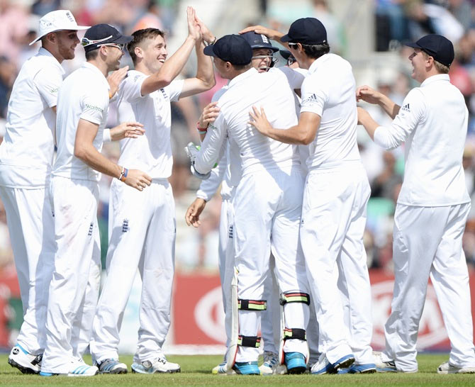 Chris Woakes of England celebrates the wicket of Murali Vijay with teammates