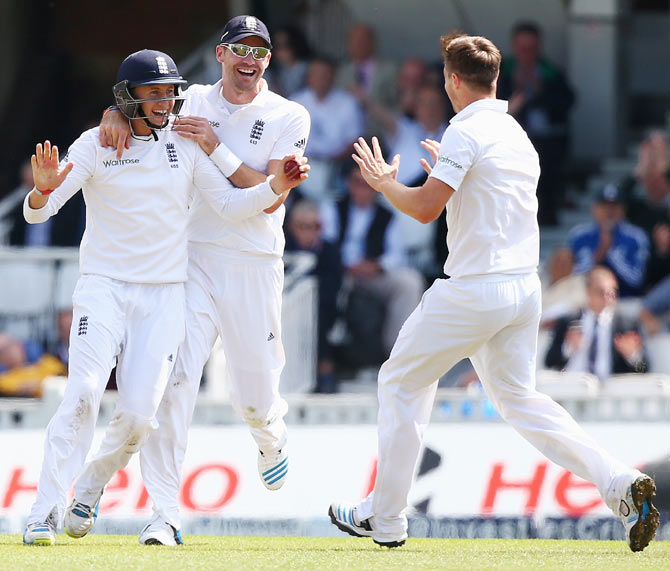 Joe Root of England (left) celebrates with James Anderson (centre) and Chris Woakes (right) after catching out Murali Vijay  on Friday