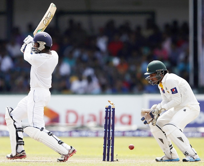 Sri Lanka's Upul Tharanga, left, is bowled out by Pakistan's Abdur Rehman (not pictured) as Pakistan's wicketkeeper Sarfraz Ahmed celebrates