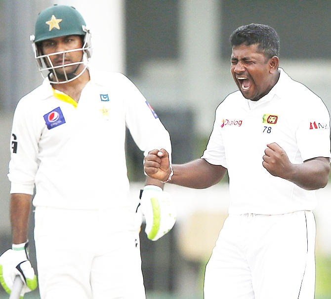 Sri Lanka's Rangana Herath, right, celebrates taking the wicket of Pakistan's Asad Shafiq (not pictured)