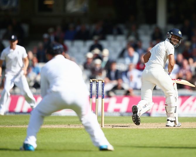Virat Kohli of India looks back as he is caught out by Alastair Cook of England