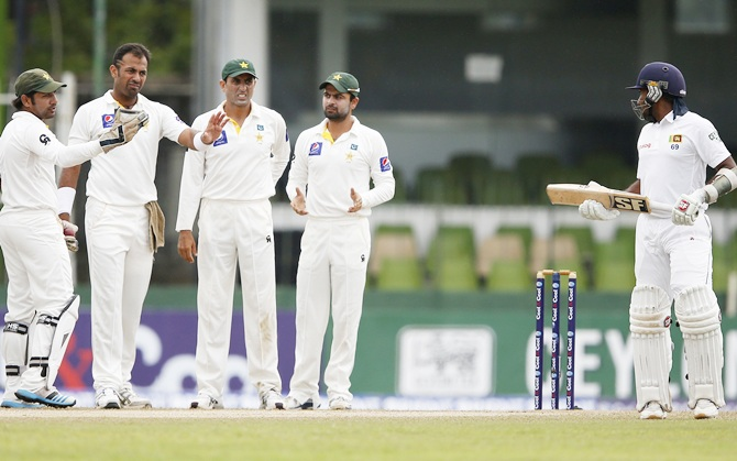 Pakistan's wicketkeeper Sarfraz Ahmed,left, Wahab Riaz, second left, Younis Khan, centre, and Ahmed Shehzad, second right, ask Mahela to wait for the third umpire decision, after umpire Richard Illingworth (not pictured) signal as Jayawardene out