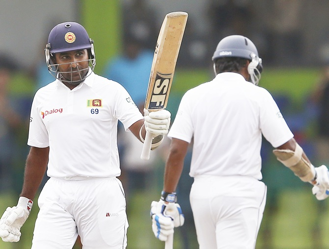 Sri Lanka's Mahela Jayawardene, left, celebrates his final Test cricket half century next to Kumar Sangakkara