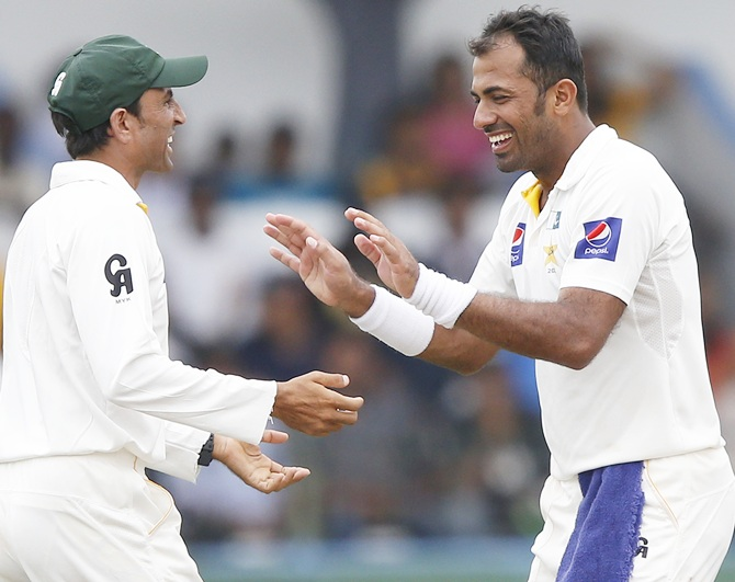 Pakistan's Wahab Riaz, right, celebrates with teammate Younis Khan after taking the wicket of Sri Lanka's Rangana Herath (not pictured)
