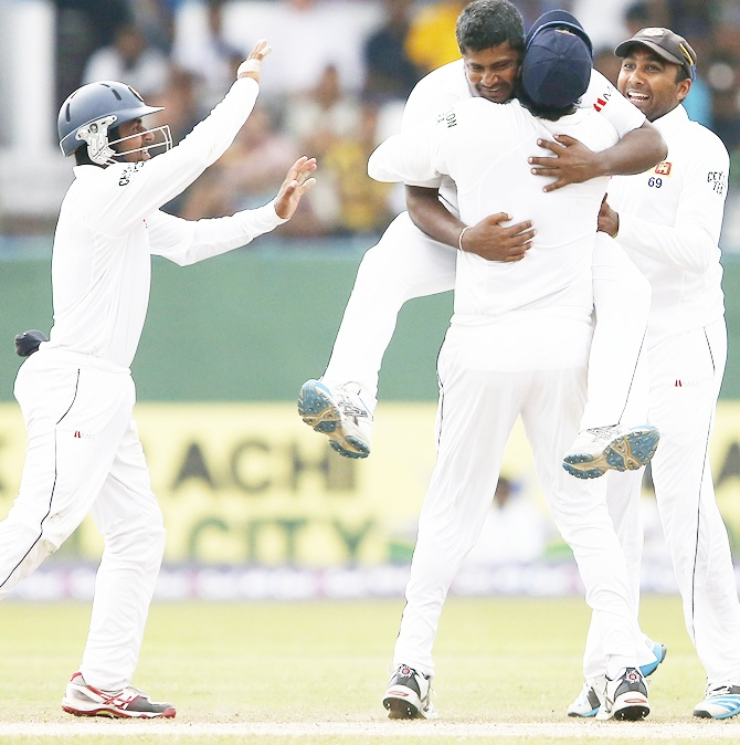 Sri Lanka's Rangana Herath (top) celebrates with captain Angelo Mathews, Mahela Jayawardene, right, and Kaushal Silva after taking the wicket of Pakistan's Asad Shafiq (not pictured)