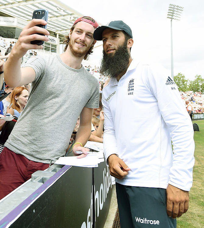 England bowler Moeen Ali poses for a selfie with a fan