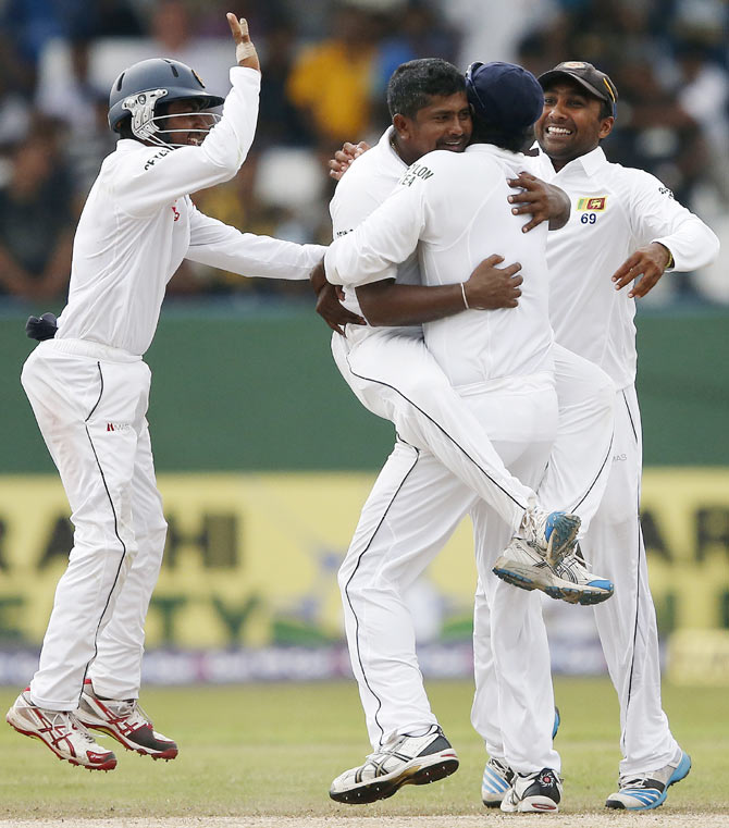 Sri Lanka's Rangana Herath (top) celebrates with captain Angelo Mathews, Mahela Jayawardene (right) and Kaushal Silva after taking the wicket of Pakistan's Asad Shafiq (not pictured) during the fourth day of their second and final Test match in Colombo on Sunday