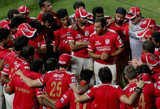 Sanjay Bangar, centre, chats with the Kings XI Punjab players during an IPL match