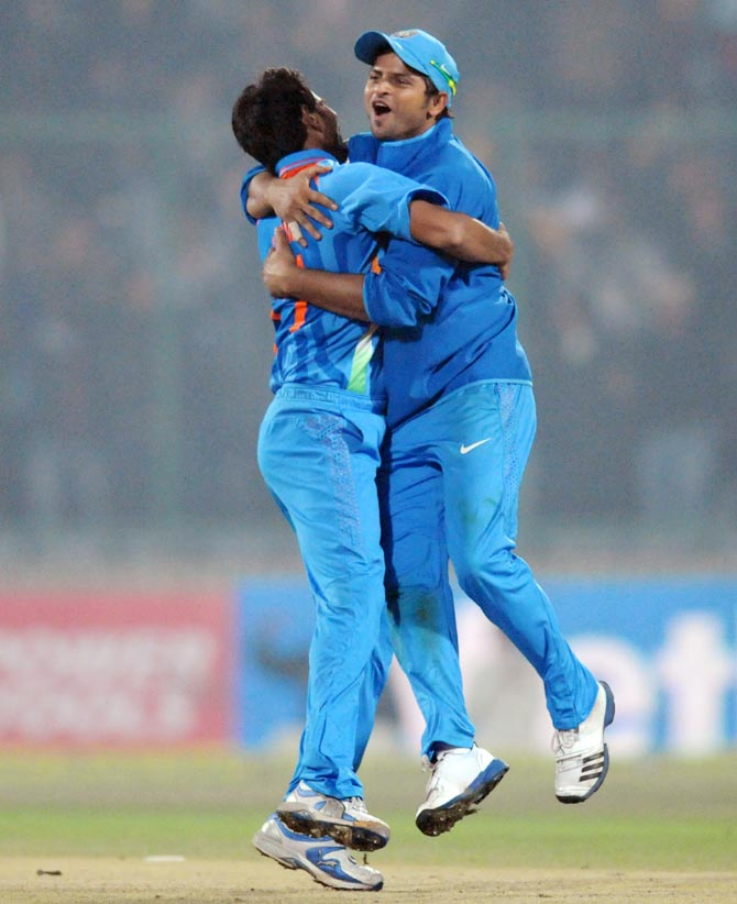 Suresh Raina (right) celebrates a wicket with Mohammed Shami