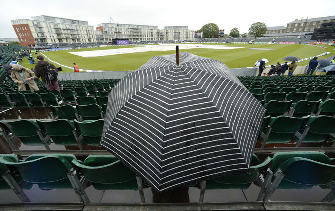 A spectator sits under an umbrella waiting for play to start in Bristol