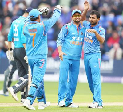 Left to right: Mahendra Singh Dhoni, Suresh Raina and Mohammed Shami celebrate the fall of an English wicket in the second ODI in Cardiff on Wednesday.,