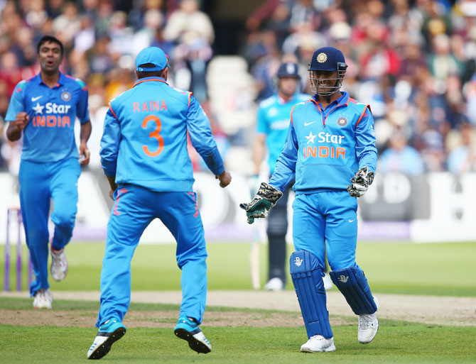 Mahendra Singh Dhoni and Suresh Raina of India celebrate the dismissal of England's   Ben Stokes, off Ravichandran Ashwin