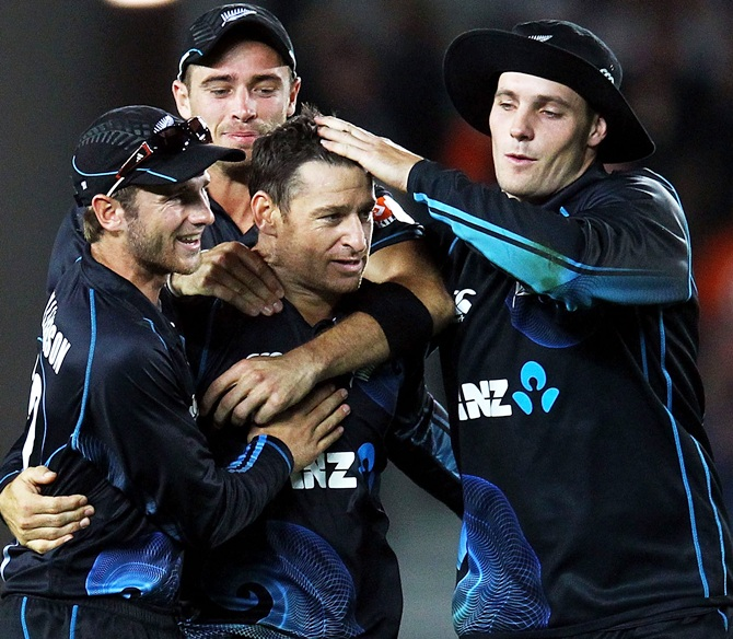 Nathan McCullum (centre) of New Zealand is congratulated by teammates