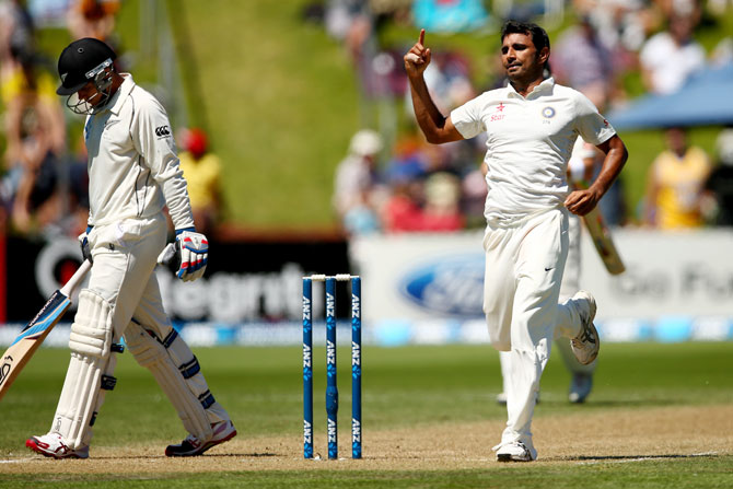 Mohammed Shami of India celebrates his wicket of Tom Latham of New Zealand (left)