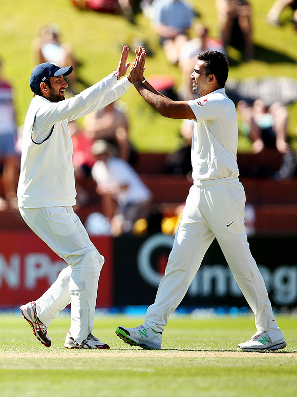 Zaheer Khan of India (right) celebrates the wicket of Kane Williamson with Cheteshwar Pujara on Sunday