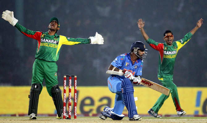 Bangladesh's wicketkeeper Anamul Haque (left) and Nasir Hossain appeal for the dismissal of Shikhar Dhawan (centre)