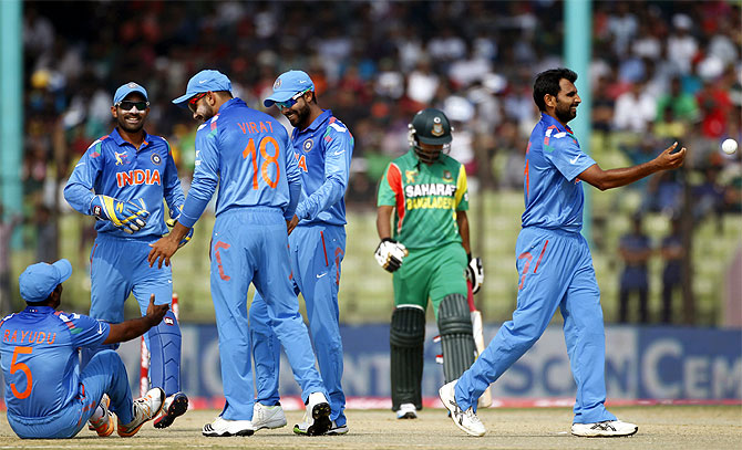 Bangladesh's Shamsur Rahman (second right) leaves the field as India's fielders celebrate his dismissal