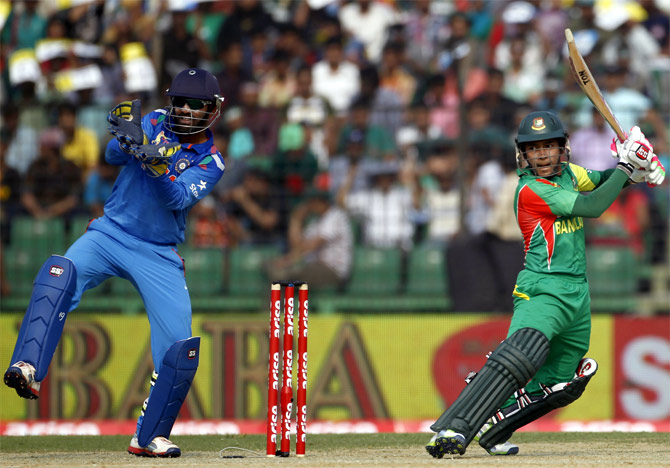 Mushfiqur Rahim hits a shot as Dinesh Karthik looks on