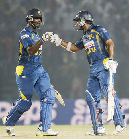 Sri Lanka's Thisara Perera congratulates Kumar Sangakkara (right) as he scores a century against India in their Asia Cup match in Fatullah