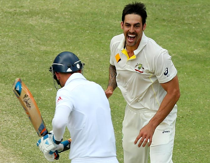 Mitchell Johnson (right) celebrates after taking the wicket of Stuart Broad