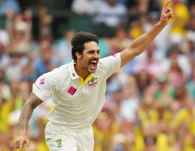 Mitchell Johnson of Australia celebrates taking the wicket of Michael Carberry of England