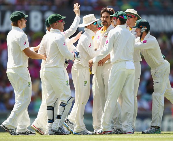 Mitchell Johnson of Australia celebrates with teammates after dismissing James Anderson of England during day two of Sydney Test