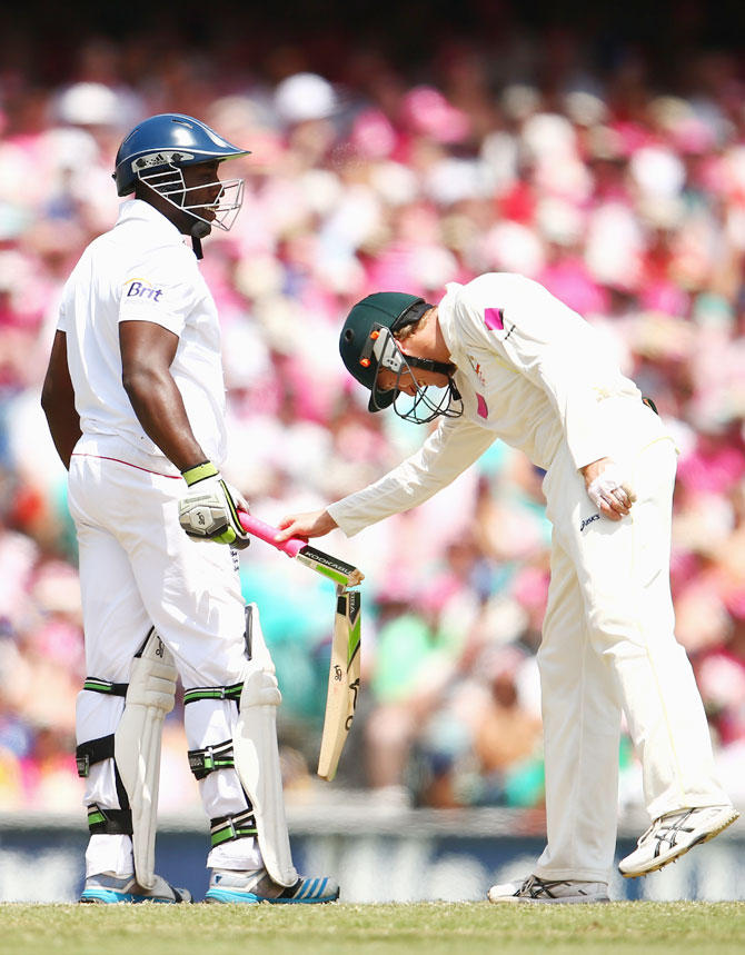 George Bailey looks at Michael Carberry's broken bat after a delivery from Ryan Harris