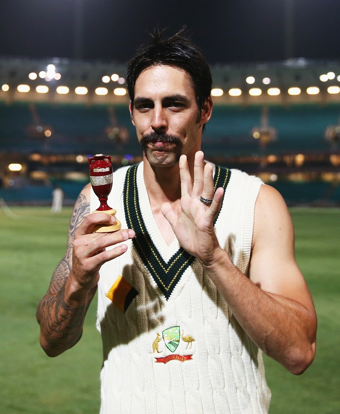 Mitchell Johnson of Australia poses with the Ashes Urn on the pitch