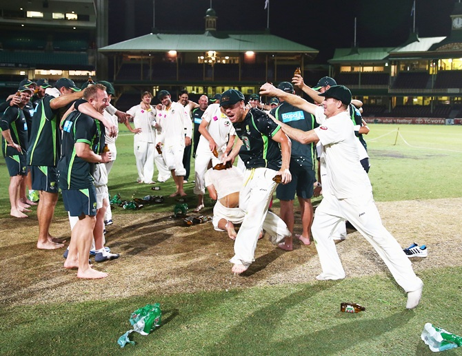 Chris Rogers of Australia pours beer on David Warner of Australia before singing the team song on the pitch