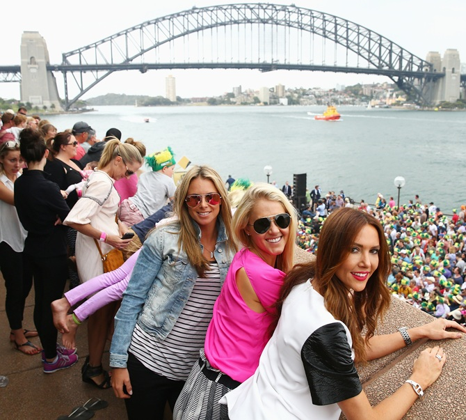 Candice Falzon (left), partner of David Warner and Kyly Clarke (extreme right), wife of Michael Clarke look on during Australian Ashes team celebrations at Sydney Opera House
