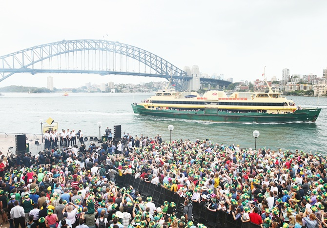 Members of the Australian Ashes team pose in front of fans at Sydney Harbour