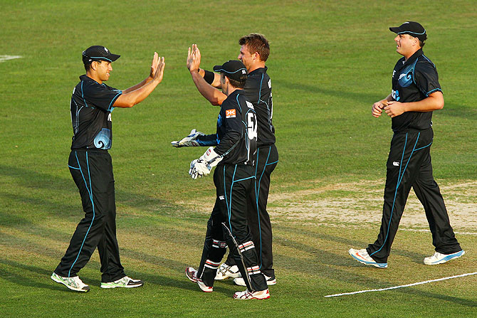 Ross Taylor of New Zealand is congratulated by Luke Ronchi, Corey Anderson and Jesse Ryder after taking a catch to dismiss Shikhar Dhawan of India